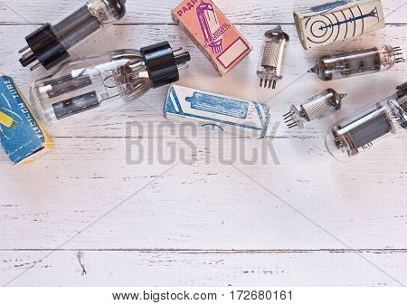 Vintage electronics board with different vacuum tubes and packaging them on white wooden background. Flat lay.
