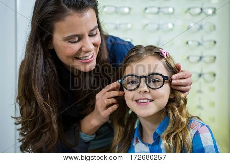 Mother prescribing spectacles to her daughter in optical store