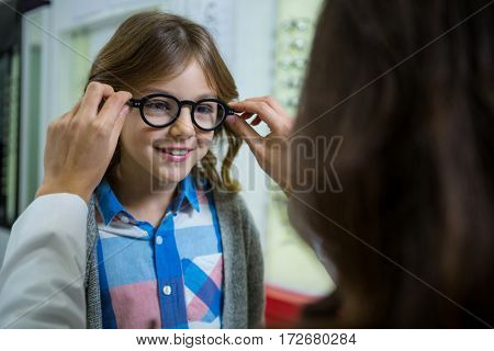 Female optometrist prescribing spectacles to young patient in optical store