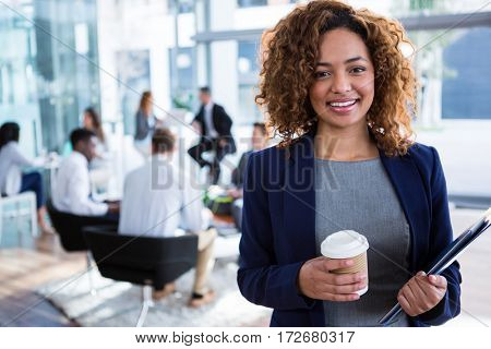 Portrait of smiling businesswoman holding coffee in office