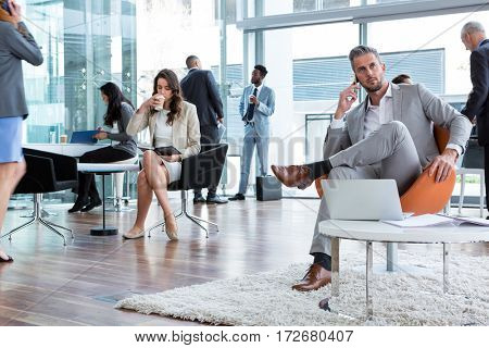Businessman talking on mobile phone with laptop on table in office