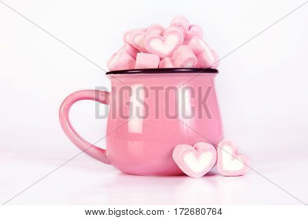 the marshmallow heart shape in cup on pink background with love concept