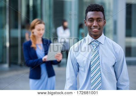 Portrait of smiling businessman standing in office building