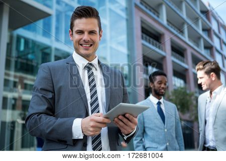 Portrait of smiling businessman using digital tablet in the office building