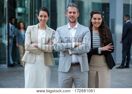 Portrait of smiling businesspeople standing with arms crossed in office building