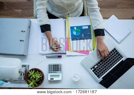 Businesswoman using laptop while writing in notepad in office