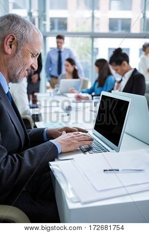 Attentive businessman working on laptop in office