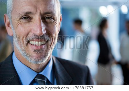 Close-up of smiling businessman standing in office
