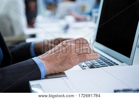 Mid section of businessman working on laptop in office