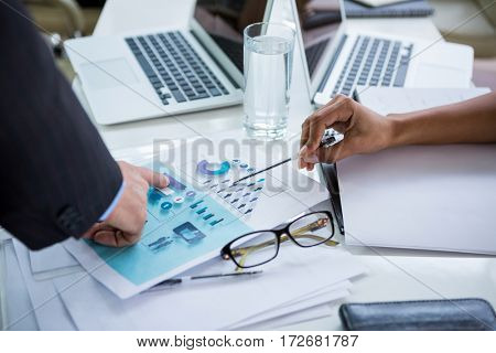 Businesspeople at desk discussing on document in office