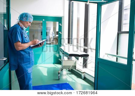 Surgeon writing on clipboard in corridor at hospital