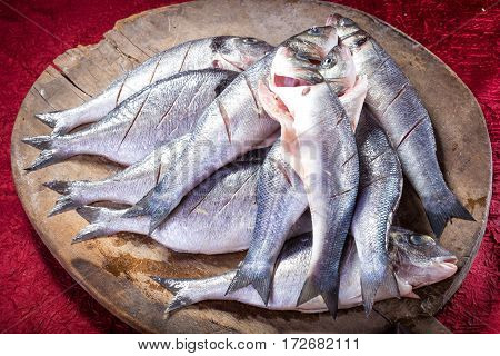 Cleaned fresh fish on wooden cutting plate ready for cooking