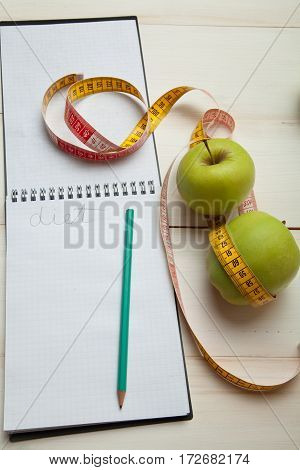 Green Apples With Measuring Tape On A White Wooden Table