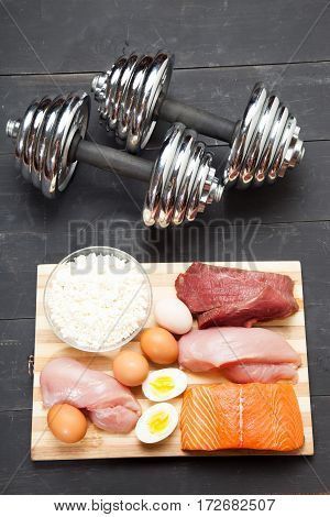 Proteins and dumbbells. Fish cheese eggs meat chicken and heart on a black wooden background