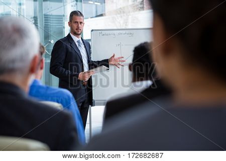 Businessman discussing on white board with co-workers in office