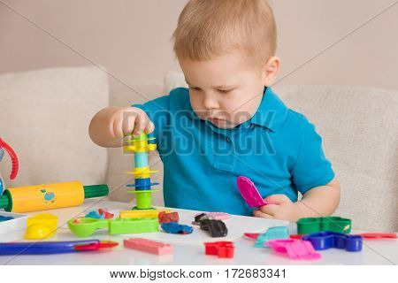 Child with colorful clay. Toddler playing and creating toys from play dough. Boy molding modeling clay.