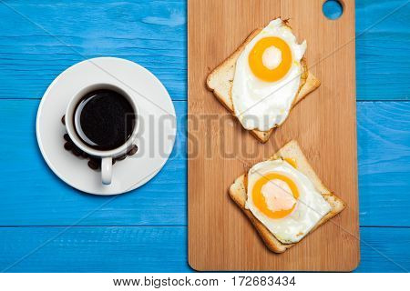 Cup With Coffee, Toast And Egg On A Blue Wooden Table