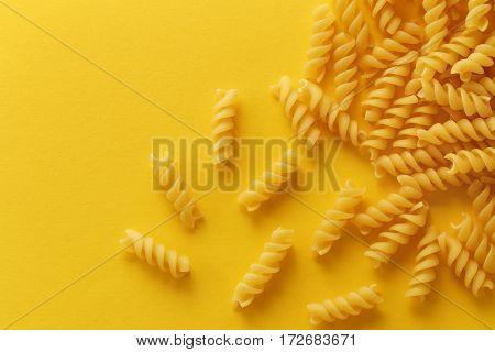 Fusilli pasta spirals on yellow background