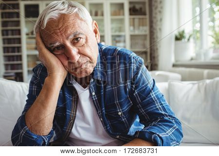 Portrait of worried senior man sitting on a sofa at home