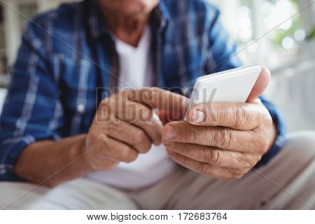 Mid-section of senior man using mobile phone at home