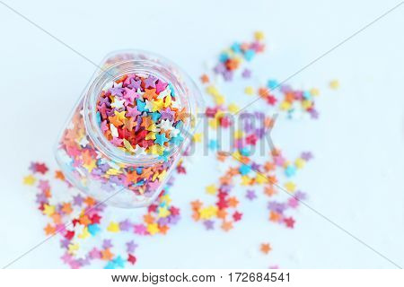 bright colored confectionery sprinkling of stars in a glass jar on a light background. soft focus blur.
