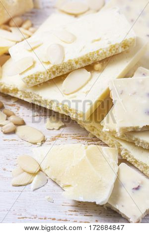 White Chocolate Pieces With Nuts On A White Wood Background