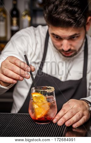 Barman putting straw into cocktail on bar counter
