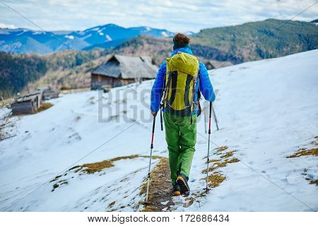 hiker with backpack on the trail in forest in the Carpathians mountains at winter