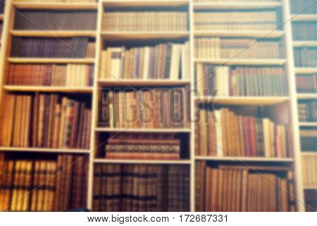 Defocused background of old books in a library - retro styled photo