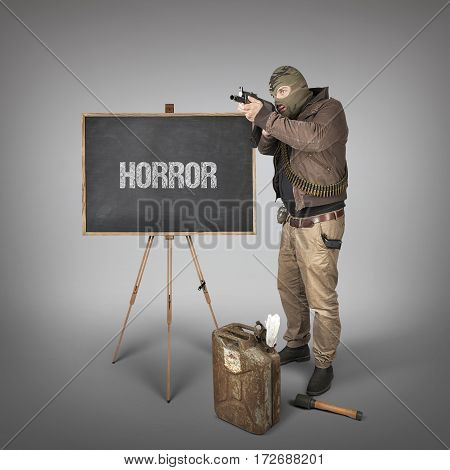 Horror text on blackboard with terrorist holding machine gun