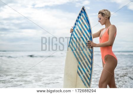 Charming girl with short hairstyle stands on the beach next to the surfboard on the background of the sea and cloudy sky. She wears orange swimsuit with sunglasses and holds her hands on the board.