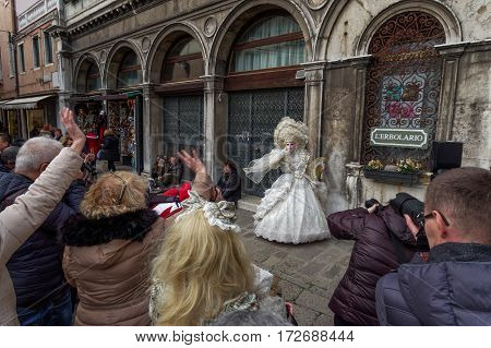 Venice, Italy - February 19 2017: Carnival mask and costume woman poses. Masked woman in traditional costume poses at a public square while people greet her during the Venice 2017 Carnival.