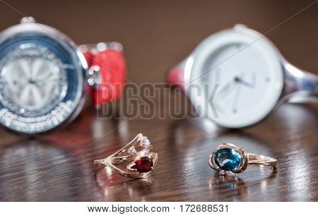 Gold Ring With Garnet And Topaz Lie On A Background Of Elegant Women's Watches