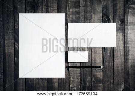 Photo of blank stationery set on wooden table background. Blank letterhead business cards envelope and pencil. Mockup for branding identity. Template for placing your design. Top view.