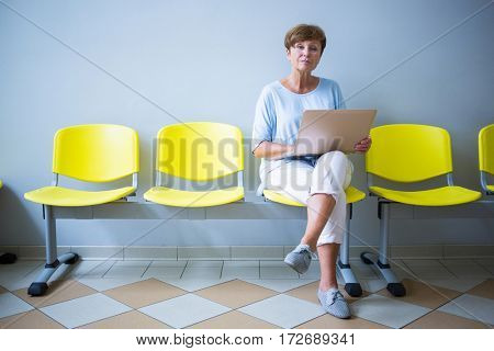 Patient sitting with report in a waiting room of a hospital