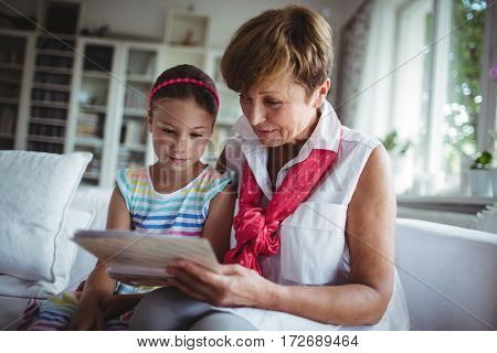Senior woman and her granddaughter looking at a photo album in home