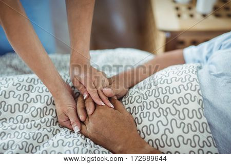 Nurse holding hands of senior woman in bedroom