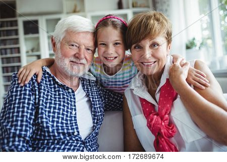 Portrait of smiling grandparents with her grand daughter at home