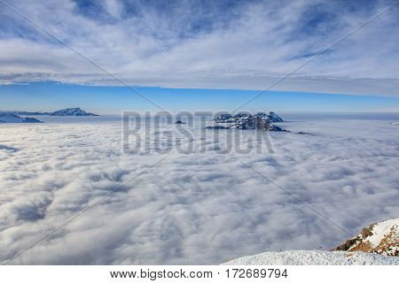 Summits of the Swiss Alps rising from sea of fog - wintertime view from Fronalpstock mountain in the Swiss canton of Schwyz.