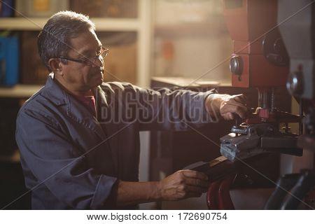 Shoemaker making shoe on machine in workshop