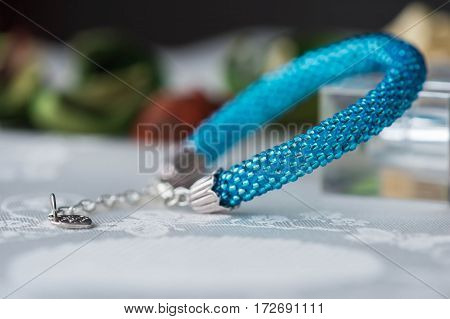 Shiny Handmade Bracelet From Beads Of Turquoise Color On Textile Background