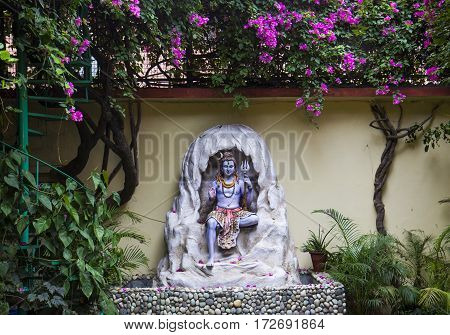 Statue of Hindu Lord Shiva under the beautiful blooming tree, Rishikesh, India