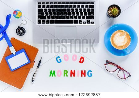Good morning. Flat lay top view office desk table. Workspace with laptop diary eyeglasses compass pen blank identification card and cup of coffee on white background.