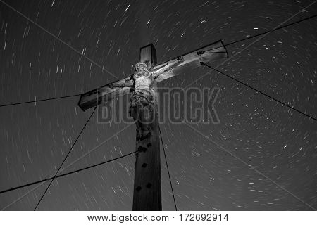 Crucifix with an illuminated Jesus statue under a clear sky with star trails.