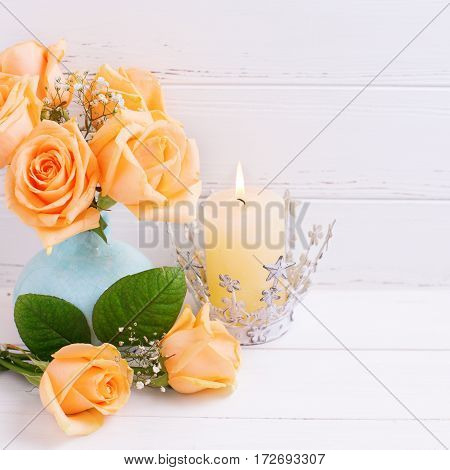 Fresh peach roses flowers in blue vase and burning candle on white wooden background. Shabby chic. Place for text. Selective focus. Square image.