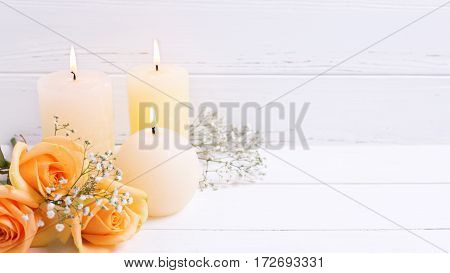 Three burning candles and peach color roses flowers on white wooden background. Shabby chic. Place for text. Selective focus. Toned image.