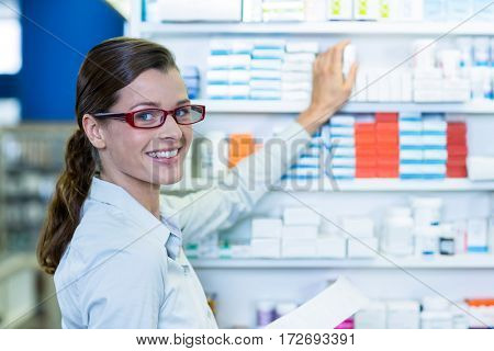 Portrait of pharmacist holding prescription while checking medicine in pharmacy