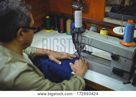 Shoemaker using sewing machine in workshop