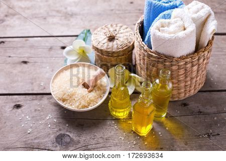 Spa or wellness setting. Bottles wih essential aroma oil towels sea salt on aged wooden background. Selective focus.