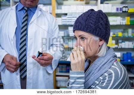 Pharmacist showing medicine to customer in pharmacy